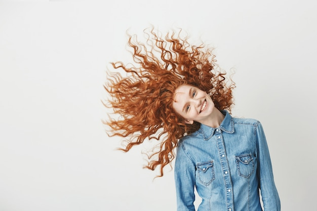Rudzielec piękna dziewczyna uśmiecha się uśmiechniętego trząść kędzierzawego włosy
