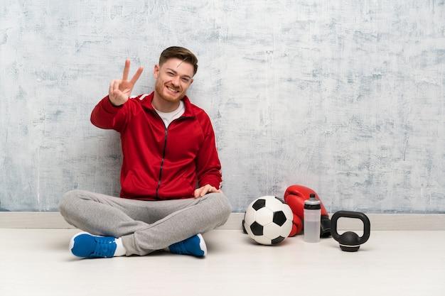 Rudzielec sporta mężczyzna uśmiecha się zwycięstwo znaka i pokazuje