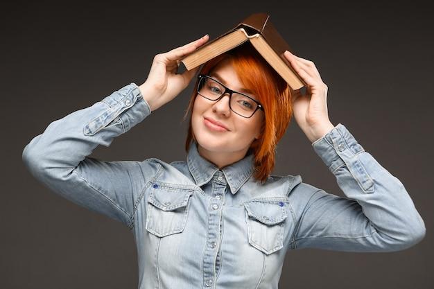 Rudzielec uśmiechnięta kobieta studiuje, trzyma książkę na głowie