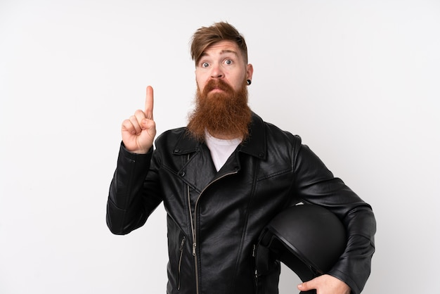 Rudzielec z długą brodą trzyma hełm motocyklowy nad odosobnioną białą ścianą wskazuje z palcem wskazującym świetny pomysł