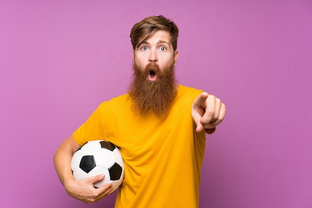 Rudzielec z długą brodą trzyma piłkę nożną nad odosobnioną purpury ścianą zaskakującą i wskazuje przód