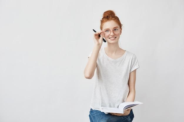Rudzielec żeński uczeń uśmiecha się korygujący szkła trzyma notatnika.