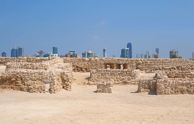 Ruiny fortu bahrajnu lub qal'at al-bahrain z nowoczesnym pejzażem miejskim manama w tle, bahrajn
