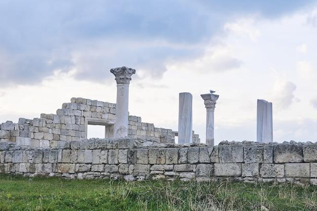 Ruiny starożytnej greckiej świątyni z kolumnami na tle zimowego pochmurnego nieba