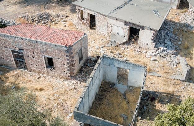 Ruiny starych domów z połamanymi ścianami i dachem w opuszczonej wiosce, widok z góry