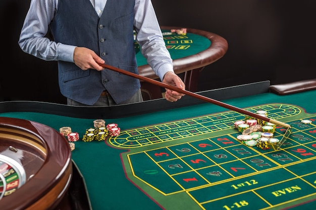 Ruletka i stosy żetonów do gry na zielonym stole w kasynie. krupier zbiera żetony za pomocą patyka
