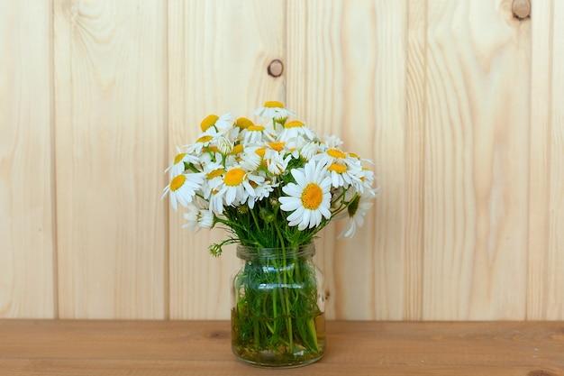 Rumianek kwiaty apteki z zielonych liści na białym tle bukiet na drewnianym stole