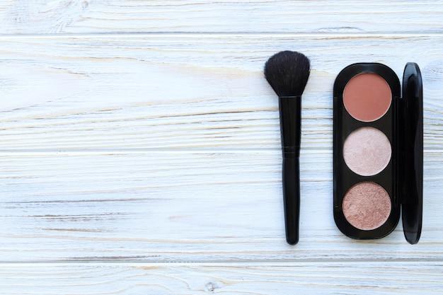 Rumieniec, rozświetlacz i pędzel do makijażu na białym drewnianym stole, miejsce na tekst, widok z góry