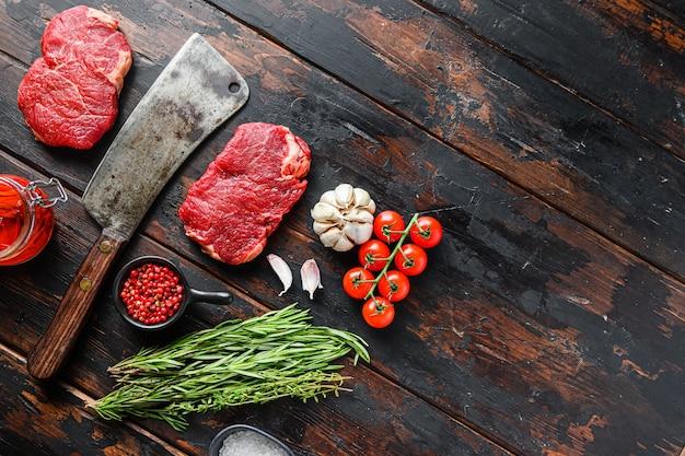 Rump stek, surowy marmurkowy stek wołowy, ze starym tasakiem rzeźnika i przyprawami na ciemnym drewnianym stole w stylu rustykalnym, widok z góry z miejscem na tekst.