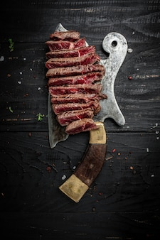 Rumszty wołowe na nóż rzeźnika mięsa z przypraw ciemnym tle. widok z góry zamknij się pionowy obraz, miejsce na tekst.