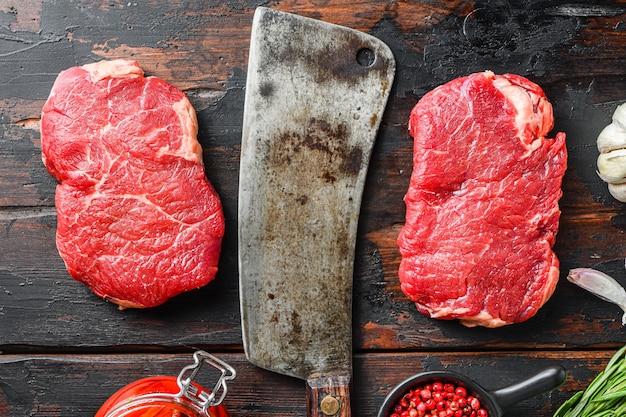 Rumsztyk pokrojony z ekologicznego mięsa, surowy marmurkowy stek wołowy, ze starym tasakiem rzeźniczym