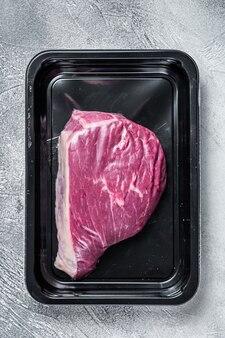Rumsztyk surowy lub stek z polędwicy wołowej w opakowaniu próżniowym. widok z góry.