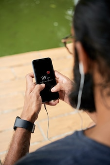 Runner man taking pulse z aplikacją mobilną
