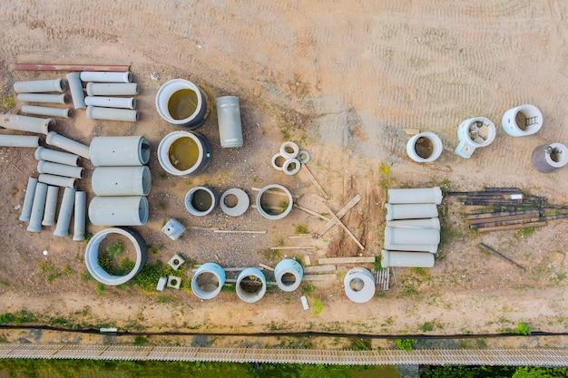 Rura ułożona w stos przy betonowych rurach drenażowych do budowy na placu budowy
