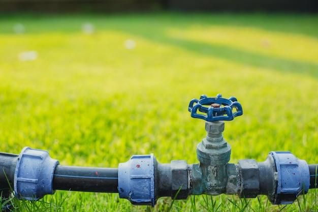 Rura zaworu wody w polu zielonej trawy ogrodowej