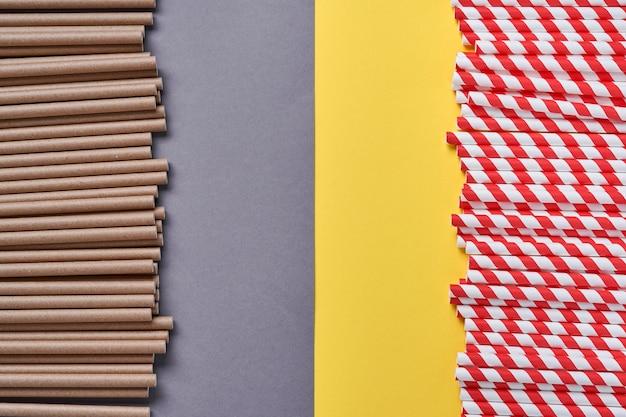 Rurki do picia czerwono-brązowe wykonane z papieru i skrobi kukurydzianej, materiału biodegradowalnego oraz szklanek z ekologicznego papieru na żółto-szarym modnym tle 2021. koncepcja bez odpadów i plastiku. widok z góry.