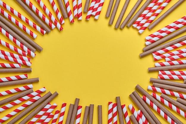 Rurki do picia wykonane z czerwonego i brązowego papieru oraz skrobi kukurydzianej, materiału biodegradowalnego na żółtym modnym tle 2021. koncepcja zero odpadów. widok z góry.