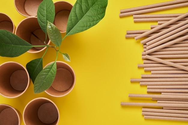 Rurki do picia wykonane z papieru i skrobi kukurydzianej, biodegradowalnego materiału i ekologicznych papierowych szklanek z zielonymi pędami liści na żółtym tle trendu 2021 koncepcja braku odpadów i plastiku. widok z góry
