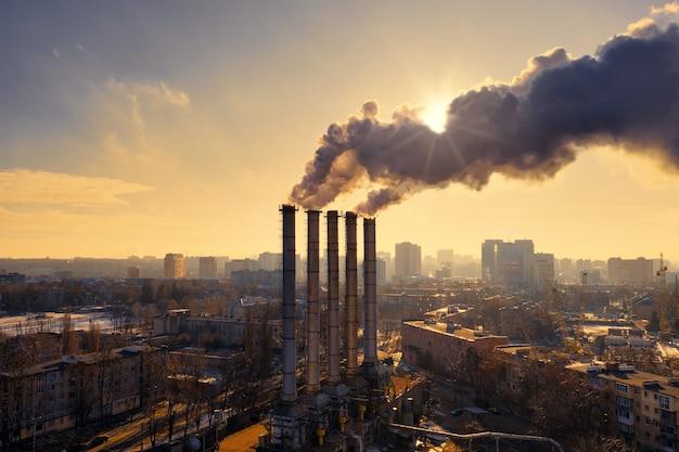 Rury fabryki przemysłowej z czarnym dymem zasłaniającym słońce podczas żółtego zachodu słońca zimą w mieście