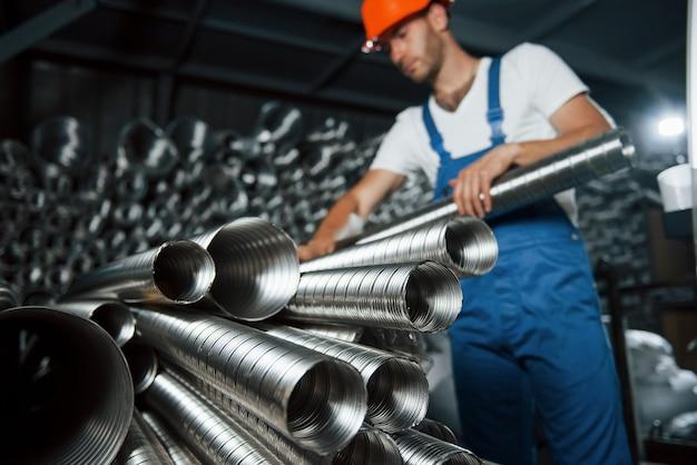 Rury wentylacyjne w kolorze srebrnym. mężczyzna w mundurze pracuje nad produkcją. nowoczesna technologia przemysłowa.