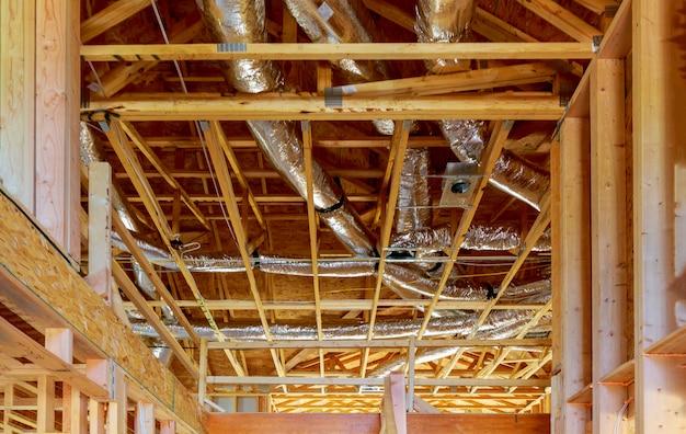 Rury wentylacyjne w srebrnym materiale izolacyjnym zwisające z sufitu wewnątrz nowego budynku.