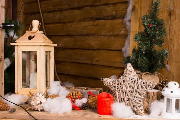 Rustykalna bożonarodzeniowa martwa natura z ręcznie wykonanymi dekoracjami, w tym drewnianą latarnią, gwiazdą splecionych gałązek, świecami i śniegiem kapokowym we wnętrzu drewnianej chaty lub chaty