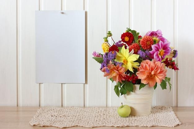 Rustykalna makieta z kartką papieru na ścianie i bukietem dalii ogrodowych. wnętrze kuchni, kwiaty i jabłko. miejsce na kopię.