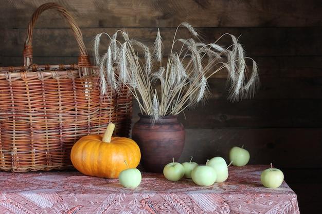 Rustykalna martwa natura z kłosami żyta, jabłkami i dynią na stole.