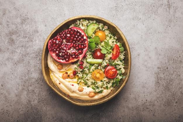 Rustykalna miska z sałatką z kuskusu z warzywami, hummusem i świeżo pokrojonym granatem. posiłek w stylu bliskowschodnim lub arabskim z przyprawami i świeżą kolendrą. zdrowa śródziemnomorska kolacja, stonowany obraz