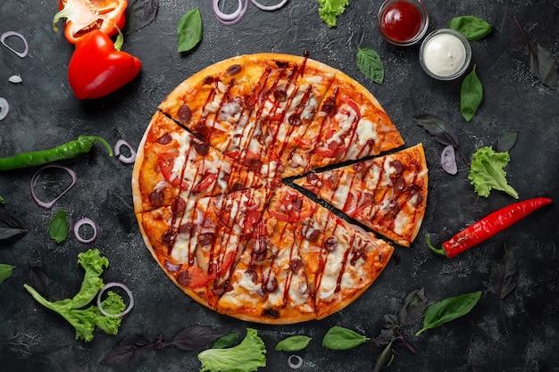 Rustykalna pizza na ciemnym tle z warzywami, papryką, mozzarellą i bazylią. widok z góry na ciemny kamienny stół