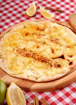 Rustykalna pizza z serem, jabłkiem i cynamonem serwowana na drewnianej desce na obiad we włoskiej restauracji