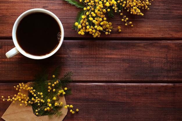 Rustykalna wiosenna kartka z kwiatami mimozy i filiżanką kawy