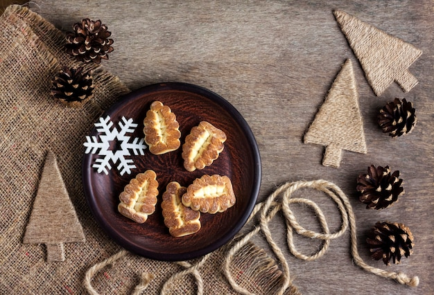 Rustykalna zimowa kompozycja z kruchego ciasteczka na talerzu i szyszki