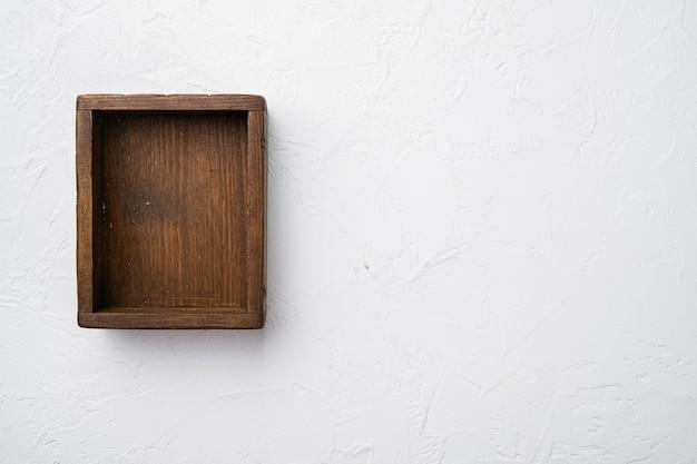 Rustykalne drewniane pudełko lub pojemnik z kopią miejsca na tekst lub jedzenie, widok z góry płasko leżący, na białym tle kamiennego stołu