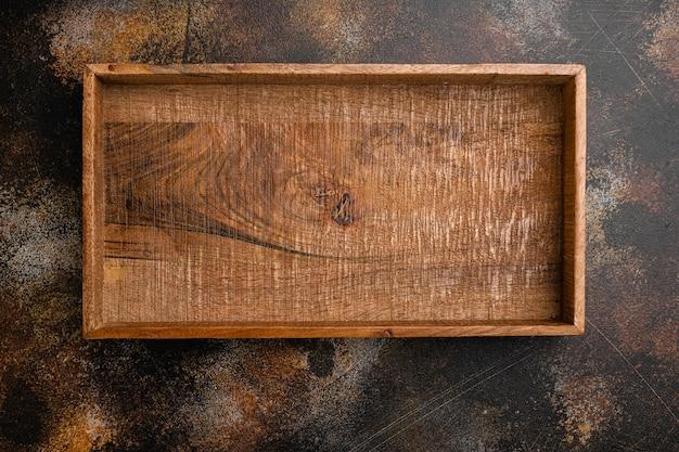 Rustykalne drewniane pudełko lub pojemnik z kopią miejsca na tekst lub jedzenie, widok z góry płasko leżał, na starym ciemnym rustykalnym tle stołu