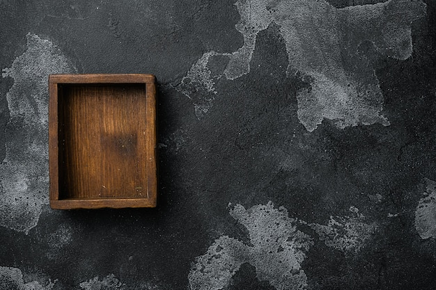 Rustykalne drewniane pudełko lub pojemnik z miejscem na kopię na tekst lub jedzenie, widok z góry płaski, na czarnym ciemnym tle kamiennego stołu