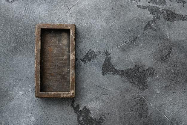 Rustykalne drewniane pudełko lub pojemnik z miejscem na kopię na tekst lub jedzenie, widok z góry płaski, na szarym tle kamiennego stołu