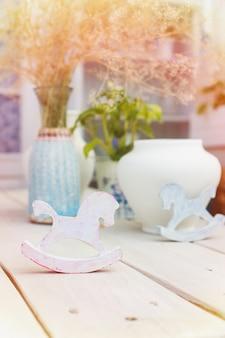Rustykalne konie na biegunach na stole w stylu provence na zewnątrz