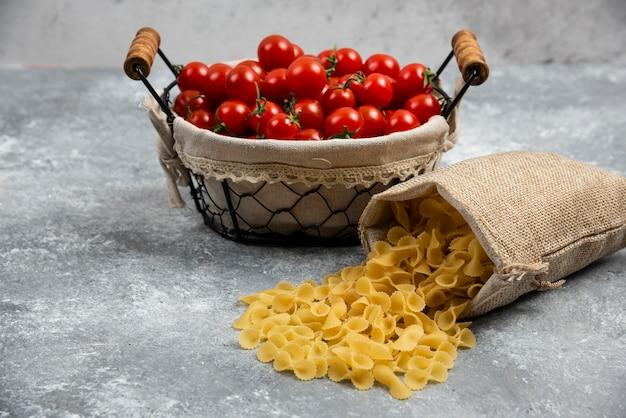 Rustykalne kosze makaronu z pomidorkami koktajlowymi na marmurowym stole.
