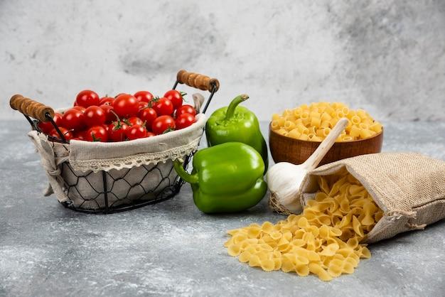 Rustykalne kosze makaronu z pomidorkami koktajlowymi, papryką i czosnkiem na marmurowym stole.