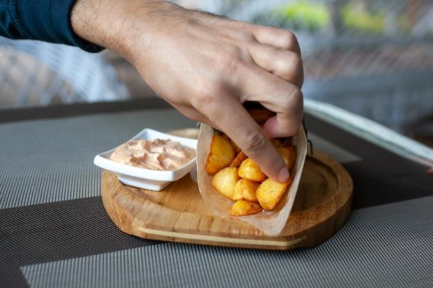Rustykalne łódeczki ziemniaczane smażone w papierowej kopercie z sosem na drewnianym talerzu na tarasie w kawiarni. mans ręka bierze kawałek i wrzuca go do sosu.