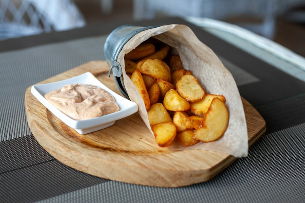 Rustykalne łódeczki ziemniaczane smażone w papierowej kopercie z sosem na drewnianym talerzu na tarasie w kawiarni.