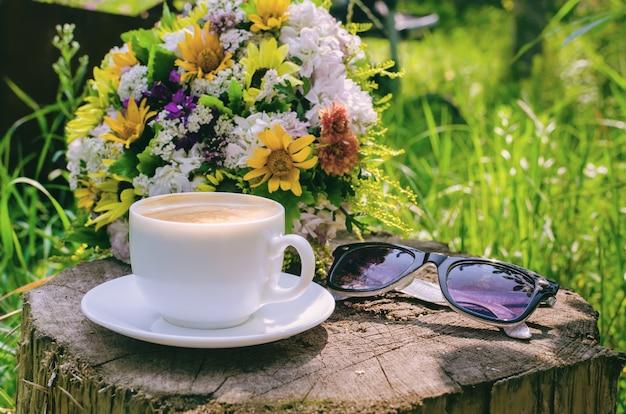 Rustykalne martwa natura - poranna filiżanka kawy i bukiet kwiatów na starym dużym pniu