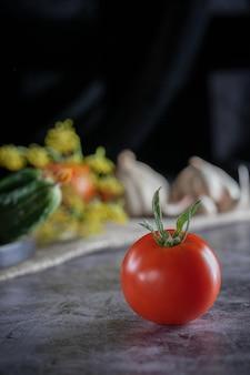 Rustykalne martwa natura ze świeżymi warzywami: czerwone pomidory, zielone ogórki, czosnek, koperek na ciemnym tle.