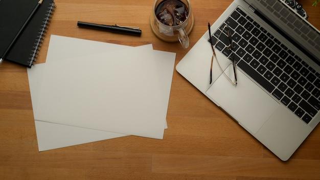 Rustykalne miejsce do pracy z laptopem, papierami, długopisem, harmonogramem, filiżanką kawy i okularami