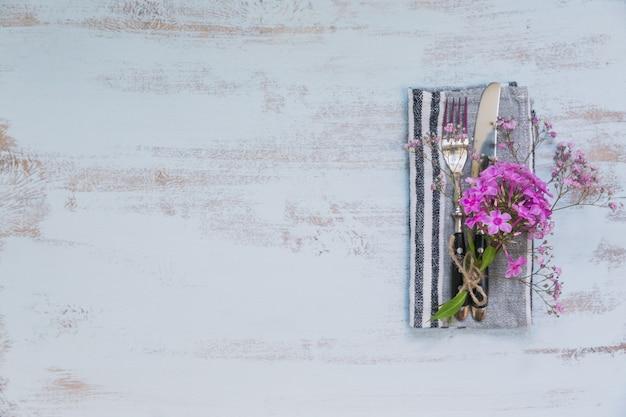 Rustykalne nakrycie stołu z różowymi kwiatami na jasnym drewnianym stole. świąteczna dekoracja w stylu prowansalskim. romantyczna kolacja. widok z góry z miejscem na kopię tekstu