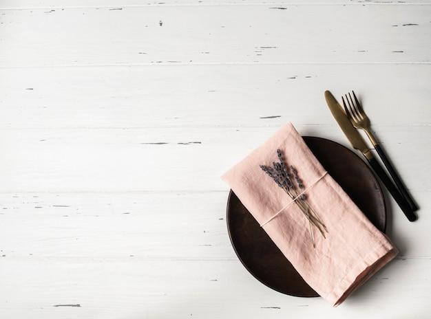 Rustykalne nakrycie stołu z talerzem, różową serwetką, lawendą i urządzeniami na białym stole z drewna. widok z góry.
