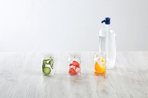 Rustykalne słoiki z lodem i różnymi nadzieniami. pomarańcza, truskawka, ogórek i mięta przygotowane do przygotowania świeżej domowej lemoniady z wodą gazowaną z syfonu.