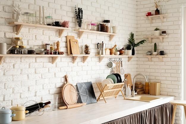 Rustykalne wnętrze kuchni z białą ceglaną ścianą i białymi drewnianymi półkami