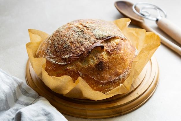 Rustykalny bochenek chleba na zakwasie, okrągły domowy chleb z dzikich drożdży. zdrowe jedzenie.